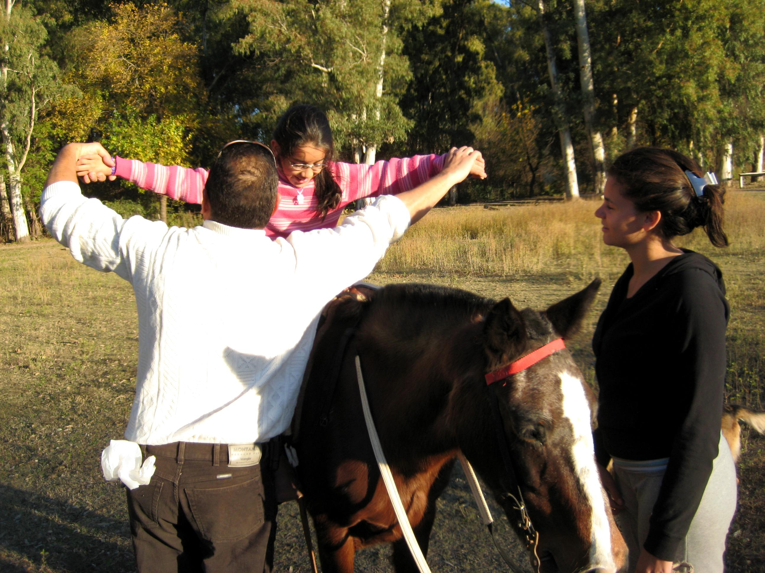 Equine Therapy interns help a young child ride a horse during a therapy session at a centre in Argentina.